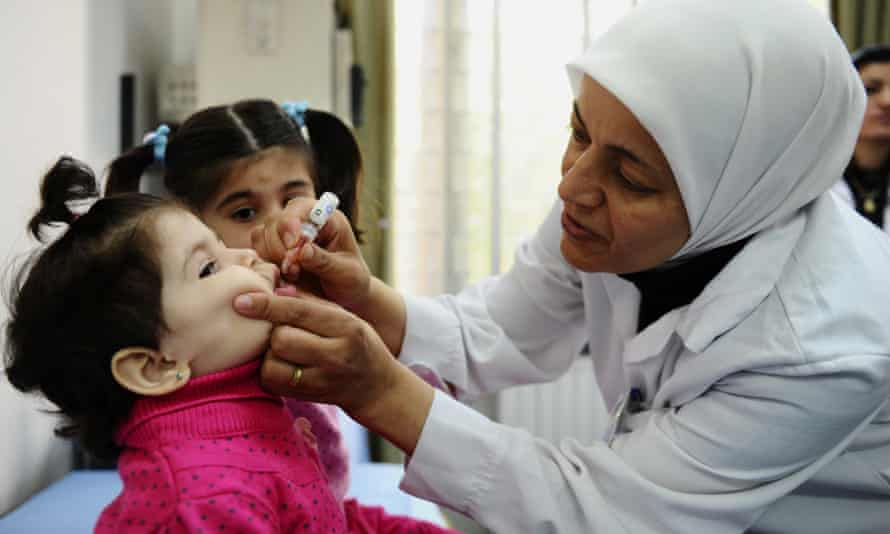 A health worker administers polio vaccine