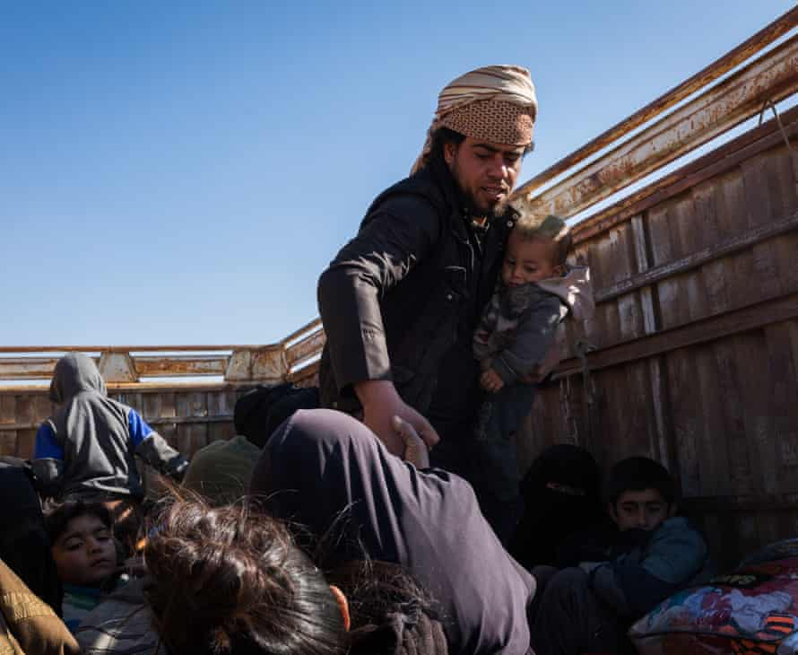 Suspected Isis families are seen inside a truck that will transport them to an IDP camp after fleeing Baghuz
