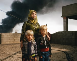 Rana, 38, with her sons, Ali and Mohammed, on the roof of their house in Qayyarah, northern Iraq