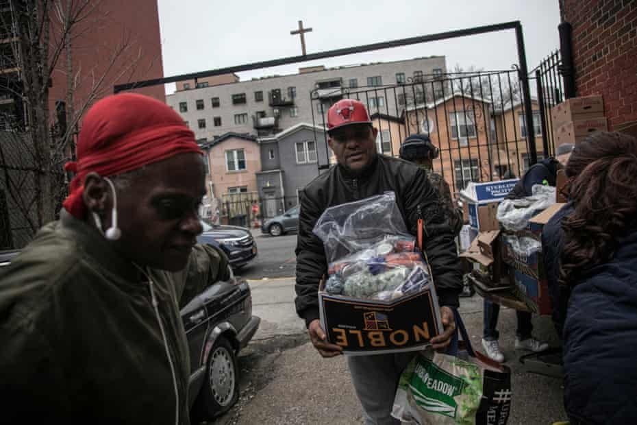 Surrounded by a few volunteers, a man carries food donations from St. Stephen Outreach in the Brooklyn borough of New York, on Friday, March 20, 2020. For decades, American nonprofits have relied on a cadre of volunteers who quite suddenly aren't able to show up. With millions staying home during the pandemic, charities that help the country's neediest are facing even greater need.