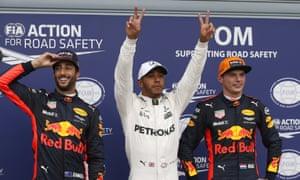 Mercedes's Lewis Hamilton celebrates pole position between Daniel Ricciardo and Max Verstappen