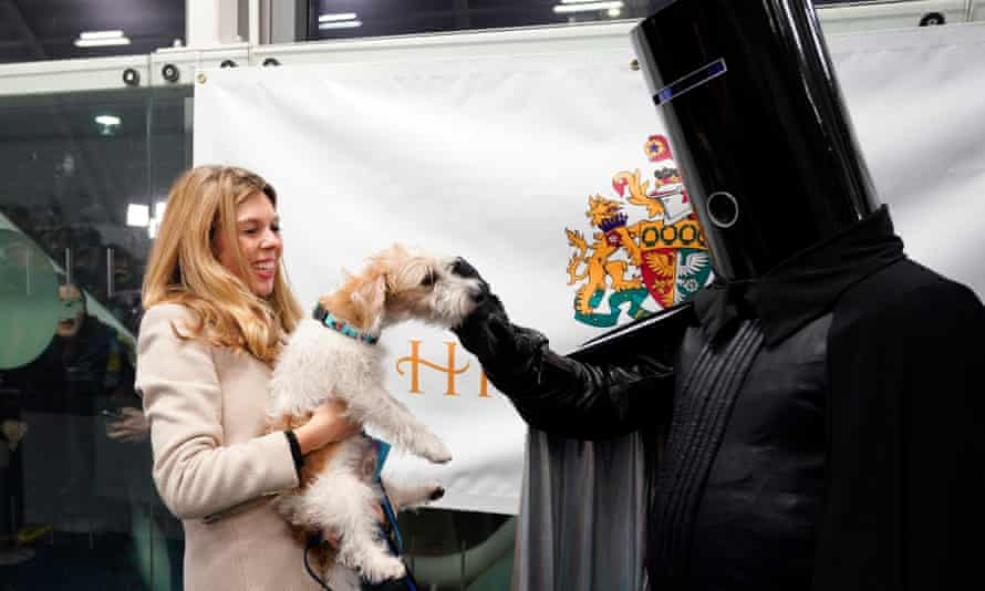 Carrie Symonds, holds Dilyn as is is petted by candidate Lord Buckethead