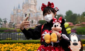 A visitor dressed in character takes a selfie at the Shanghai Disney Resort.