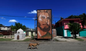 A dog walks past a painting depicting Fidel Castro by Cuban artist Kcho in Havana, Cuba, in August 2016.
