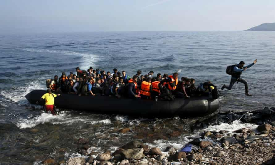 Migrants arrive on a raft on to a beach on the Greek island of Lesbos.