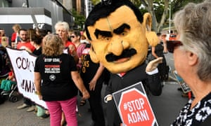A protestor wearing a mask depicting Adani Group chairman Gautam Adani is seen during a protest against the Carmichael coal mine in Brisbane.