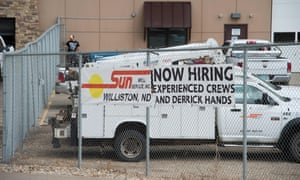 A 'now hiring' banner decked to a car park fence