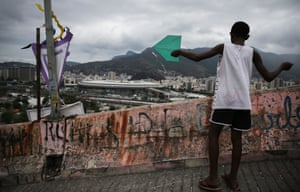 A boy plays with a kite in a favela overlooking Maracanã stadium