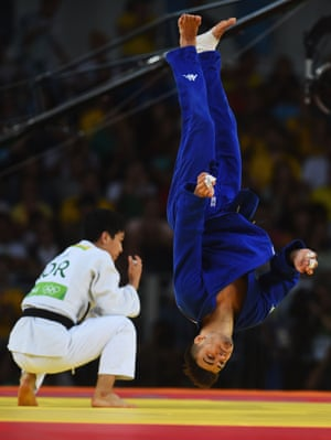 Italy's Fabio Basile celebrates his win with a flip after winning the gold medal against Baul An of Korea in the Men's -66kg.