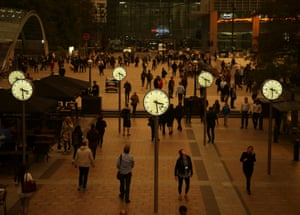 People walk in Canary Wharf while the sky overhead turns red