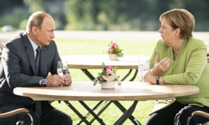Man holding glass of white wine sits across table at woman in green jacket