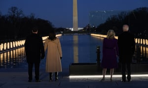 With the Washington Monument in the background, President-elect Joe Biden stands with his wife Jill Biden and Vice President-elect Kamala Harris stands with her husband Doug Emhoff as they look at lights placed around the Lincoln Memorial Reflecting Pool during a Covid-19 memorial Tuesday, January 19, 2021, in Washington.