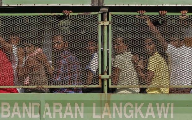Bangladeshi and Rohingya migrants are seen in a truck as they arrive at a naval base before being transferred to Kuala Kedah jetty with the navy ship 'KD Mahawangsa', in Langkawi, Malaysia, 14 May