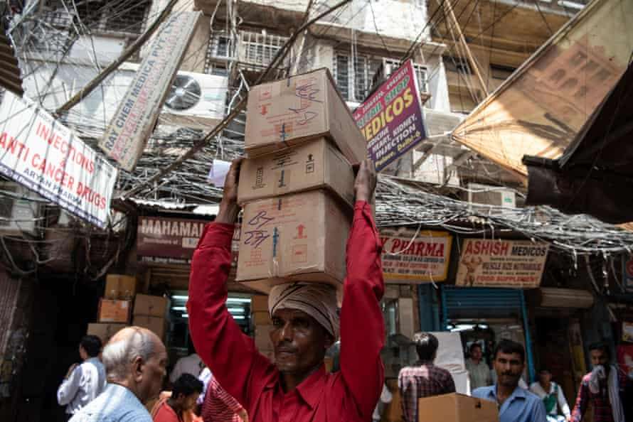 A man carries boxes of medicines to a shop in Bhagirath Palace's pharmaceuticals market, Old Delhi, India.