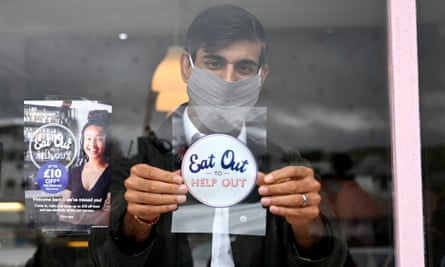 Chancellor Rishi Sunak puts an 'eat out to help out' sticker in a window