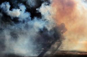 A demonstrator runs amid teargas during a protest in Santiago against Chile's state economic model.