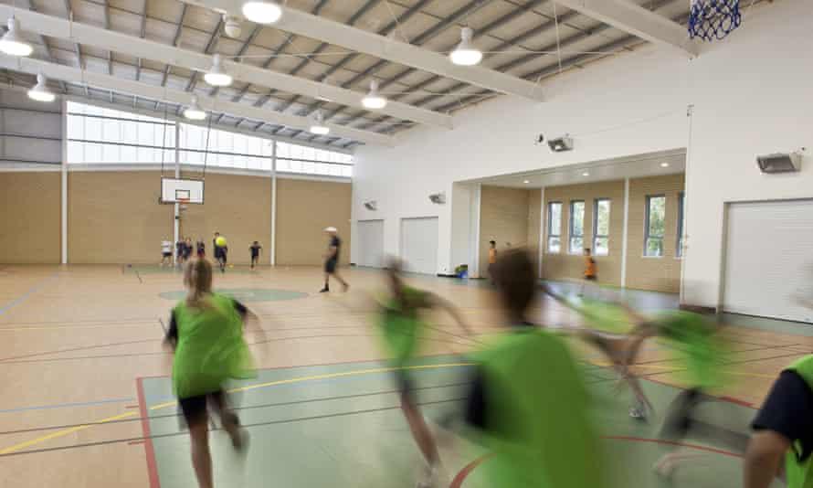 Schoolchildren exercise in an indoor sports hall.