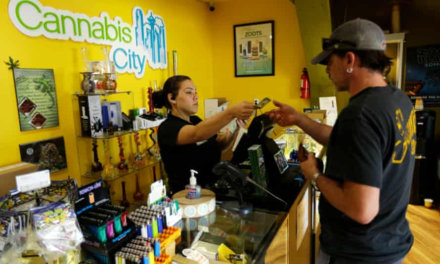 Jessica Mann, left, gives change to a customer at Cannabis City in Seattle.