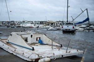 Damaged boats and a truck are seen in a marina