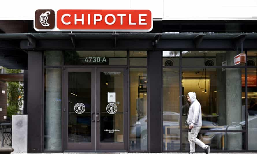A pedestrian walks past a closed Chipotle restaurant Monday in Seattle.