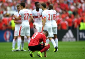 Ermir Lenjani is dejected at the final whistle as the Swiss players celebrate.