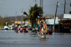 A man rides his horse on a flooded street in San Juan