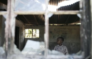 A boy inspects a house in the Kericho tea plantation compound which was burnt and looted during the unrest after the 2007 elections.