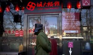 A man walks past a branch of Beijing's Huda restaurant chain