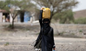 A woman carries water at a camp for internally displaced people near Sanaa, Yemen.