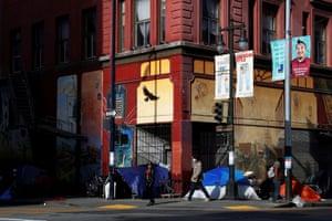 Pedestrians walk by homeless encampments in the Tenderloin.
