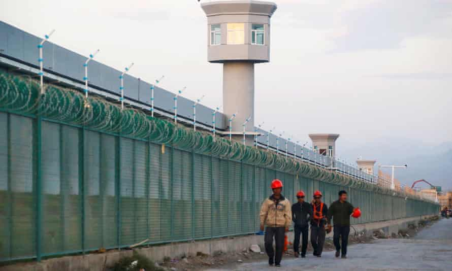 Workers walk by the fence of a detention centre for Uighurs in Xinjiang, China
