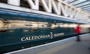 The Caledonian Sleeper speeds through a station.