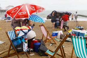 People on beach sheltering from rain