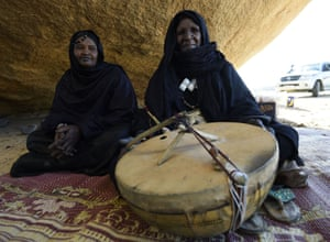 Tuareg Khoulene Alamine an imzad teacher sits with her instrument and a student on the sand