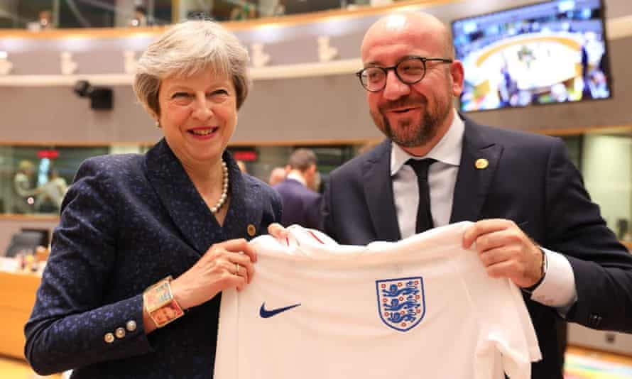 Theresa May and the Belgian prime minister hold up an England shirt at the recent EU summit