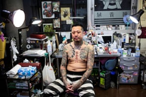 Tattoo artist H:K displays his tattoo at a studio in Tokyo
