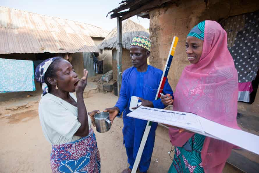 Local workers administer treatment to prevent river blindness in Nigeria, which affects about one in five people across the globe