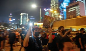 Protesters march at night in Hong Kong