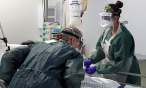 Nurses caring for a patient in an intensive care ward