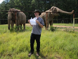 The writer holds a picture of Shirley with two elephants in the background
