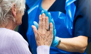 A care worker in gloves makes hand contact with elderly woman