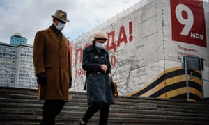 A couple wearing face masks walk in front of a banner for the upcoming Victory Day celebrations