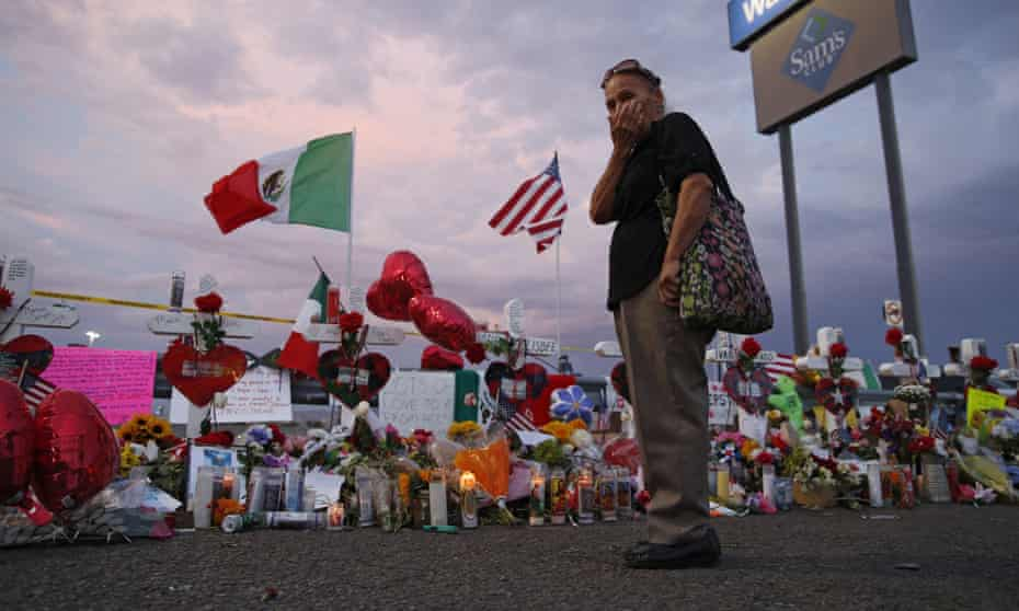 Catalina Saenz wipes tears from her face as she visits a makeshift memorial near the scene of the El Paso mass shooting