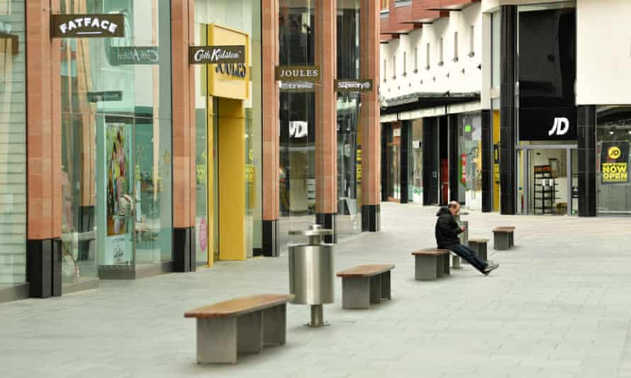 A lone member of the public sits in an empty Princesshay Shopping Centre in Exeter, England.