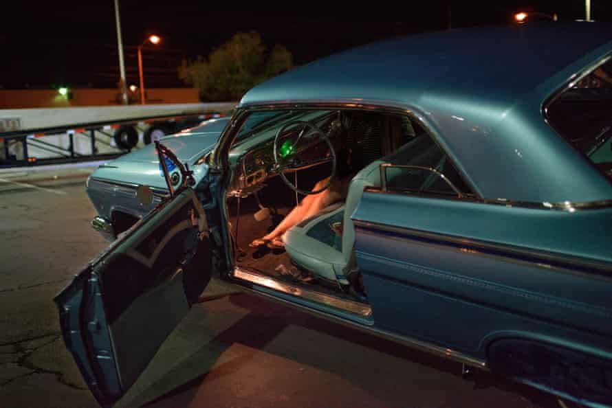 blue lowrider with woman's legs visible in front seat