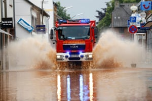 Erftstadt, Germany: A fire truck splashes through a flooded street.