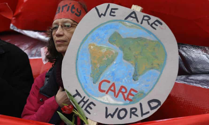 A climate activist holds up a banner showing a picture of the globe