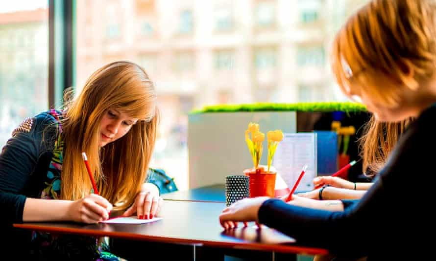Two girls write a poem in a cafe in Hungary for last year's Pay with a Poem initiative.