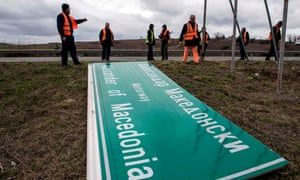 Workers remove a sign with the former name of the highway leading to the Greek border, Alexander of Macedonia, newly renamed Friendship Highway, near Skopje. The government decided to change the name of the highway, along with the name of the Skopje airport, following the name dispute with Greece.