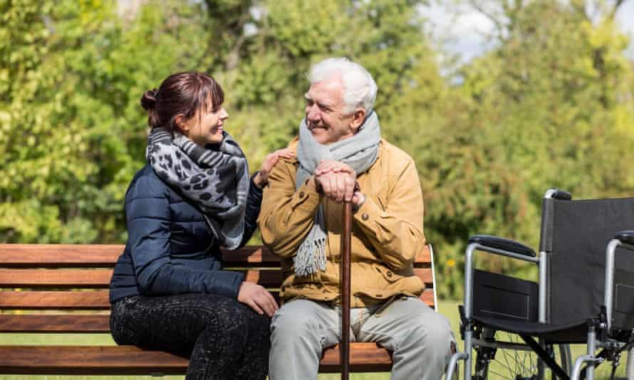 Elderly man and female carer on park bench